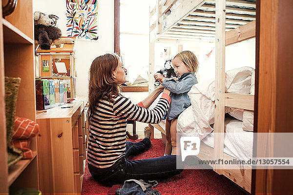 Seitenansicht der Frau  die den Sohn im Schlafzimmer anzieht