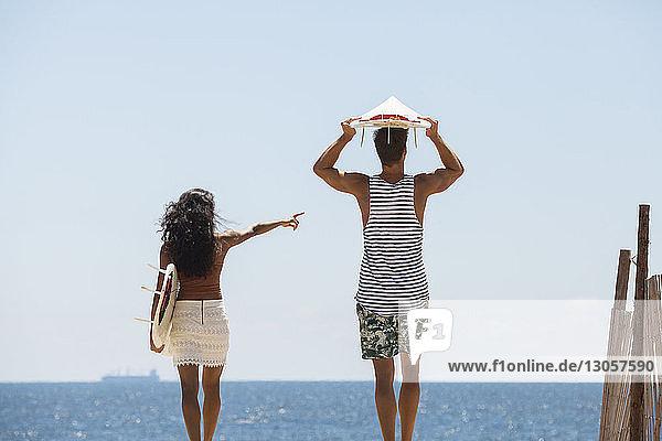 Frau zeigt auf eine Frau  während sie mit ihrem Freund am Strand steht