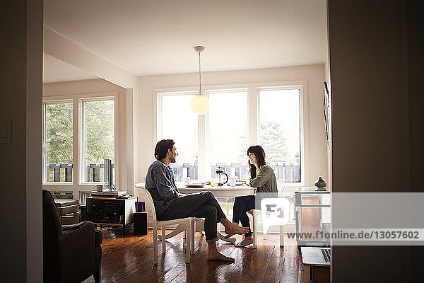 Couple sitting by breakfast table in morning at home
