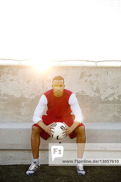 Portrait of confident sportsman holding soccer ball sitting on seat against surrounding wall on sunny day