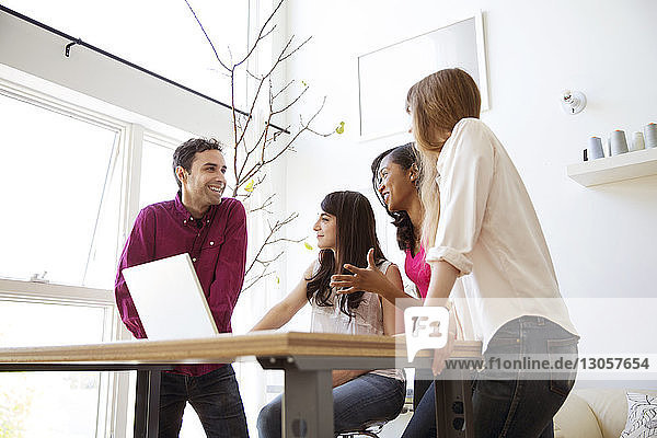 Happy business colleagues having discussion over laptop at table