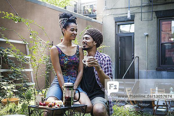 Frau sitzt auf dem Schoss des Mannes am Frühstückstisch im Rasen