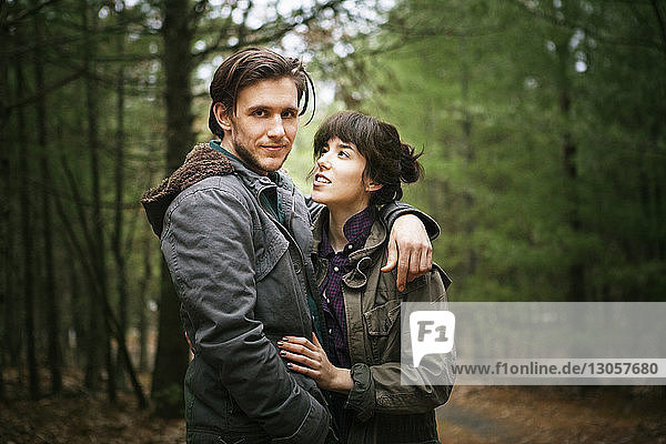 Portrait of man standing with woman in forest
