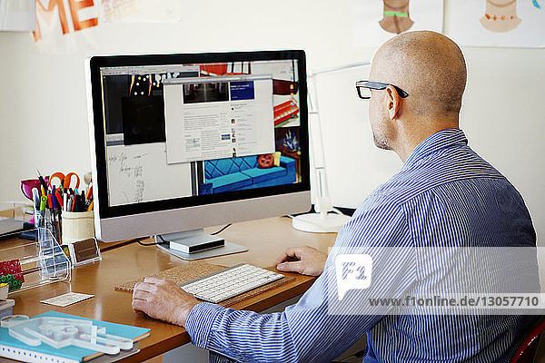Rückansicht eines Menschen  der zu Hause einen Desktop-Computer benutzt