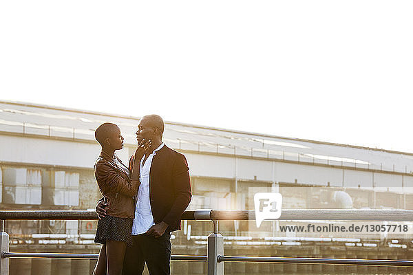 Romantic couple standing by railing against building