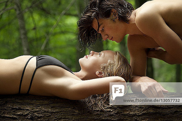 Side view of sensual couple on tree trunk