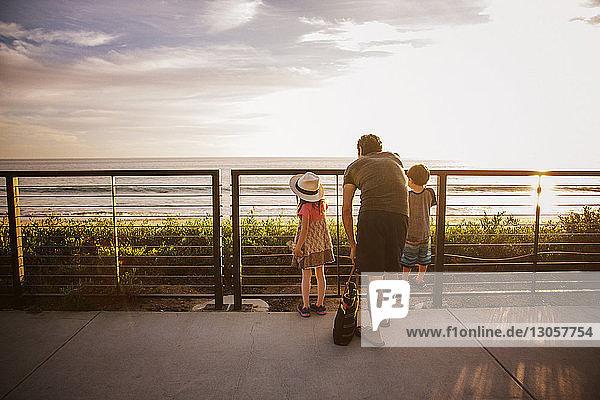 Rückansicht einer Familie,  die bei Sonnenuntergang am Geländer steht und aufs Meer schaut