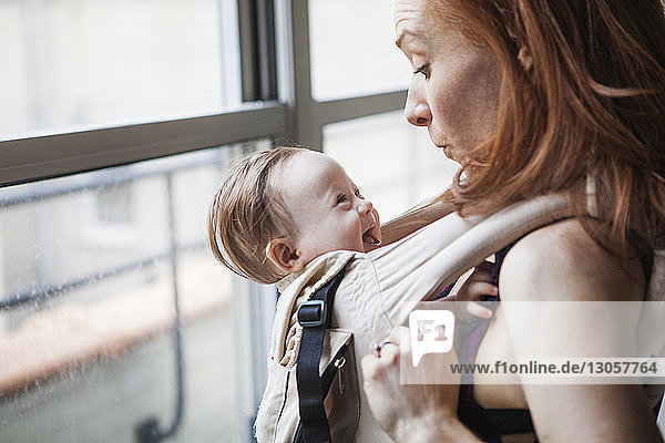 Mother playing with daughter while carrying in baby carrier at home