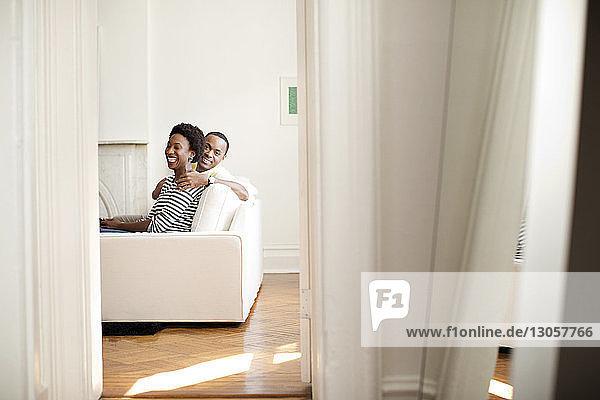 Glückliches Paar sitzt zu Hause auf dem Sofa