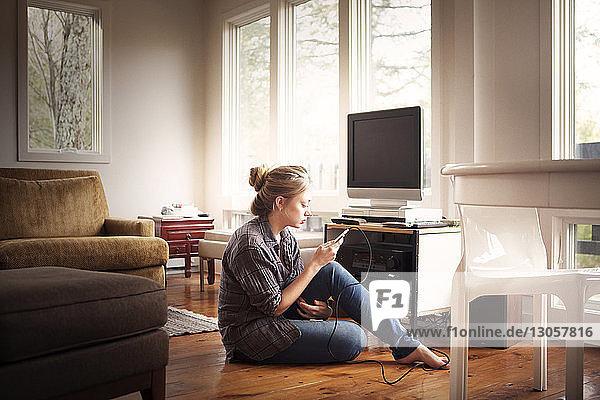 Frau benutzt Mobiltelefon  während sie zu Hause sitzt