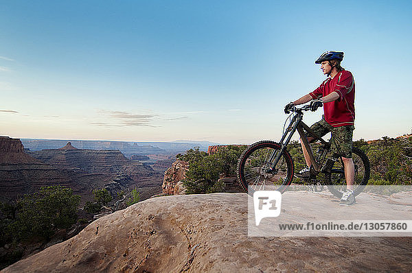 Mountain biker with bicycle looking away while standing on cliff against sky