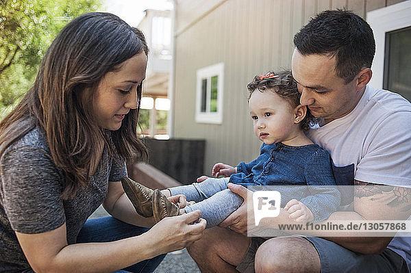 Vater trägt Baby  während Mutter beim Tragen von Schuhen hilft