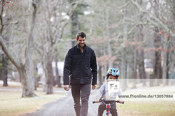 Happy father looking at son riding bicycle on road