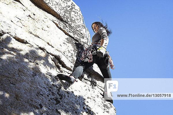 Niedrigwinkelansicht einer Frau beim Klettern vor klarem blauen Himmel