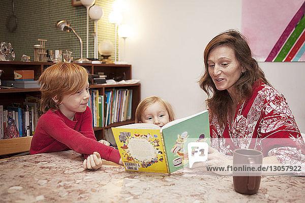 Mutter und Söhne lesen zu Hause bei Tisch Buch