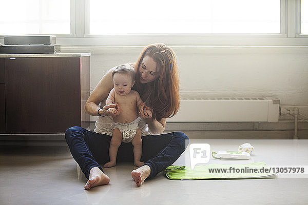 Mother holding daughter hands while sitting on floor at home