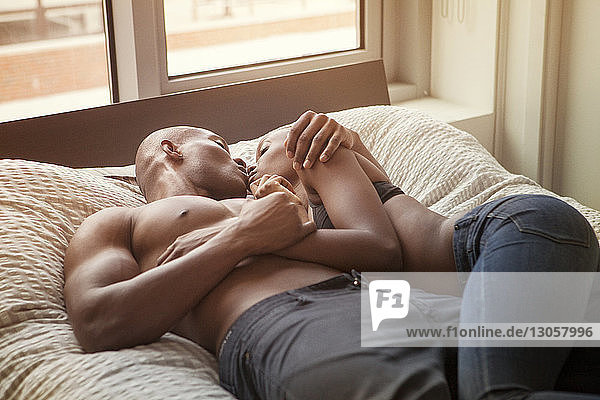 High angle view of affectionate couple on bed at home