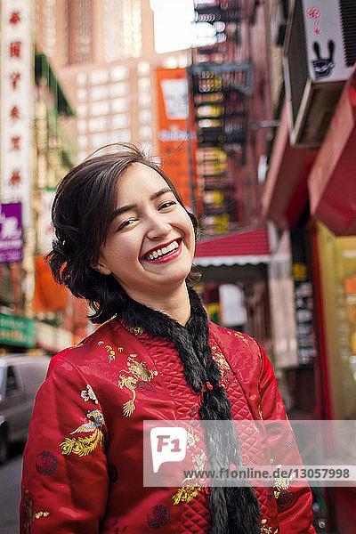 Porträt einer fröhlichen Frau in traditioneller Kleidung auf der Straße der Stadt stehend