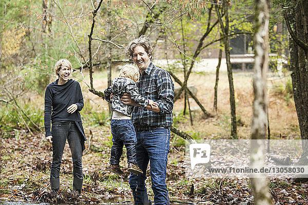 Fröhliche Familie genießt  während sie am Fluss steht
