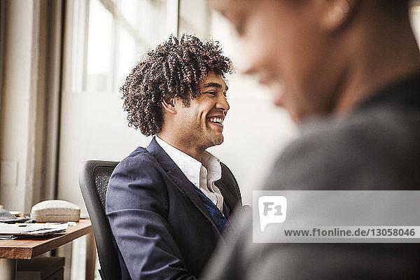 Glücklicher Geschäftsmann sitzt auf Stuhl von Bürokollegen