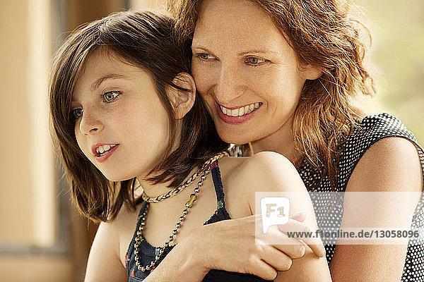 Glückliche Mutter umarmt Mädchen zu Hause
