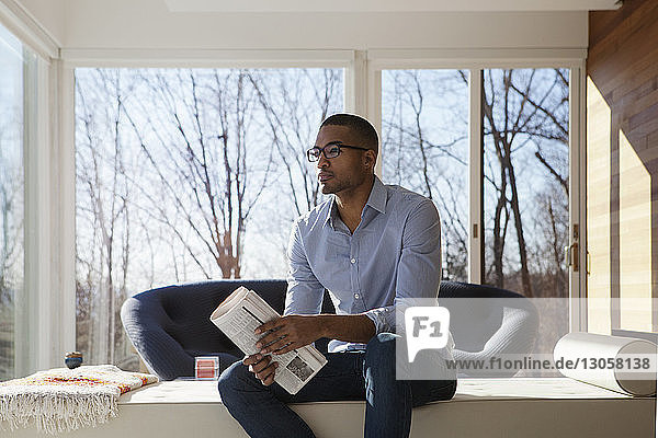 Man holding newspaper looking away while sitting on sofa at home