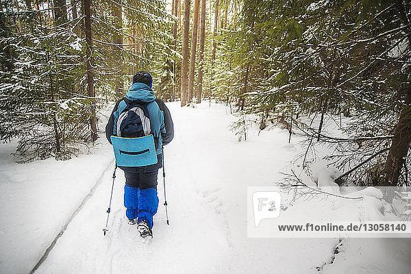 Rückansicht eines Wanderers mit Rucksack beim Wandern im verschneiten Wald