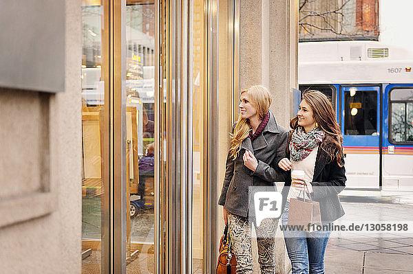Smiling women looking at store while walking on sidewalk