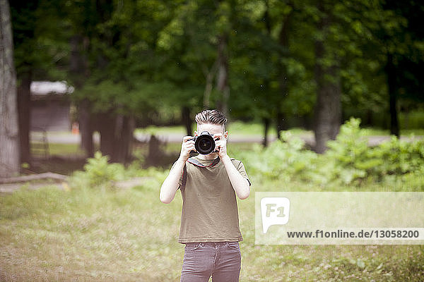 Teenage boy photographing while standing on field