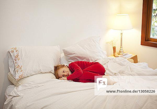 Porträt eines zu Hause auf dem Bett liegenden Jungen