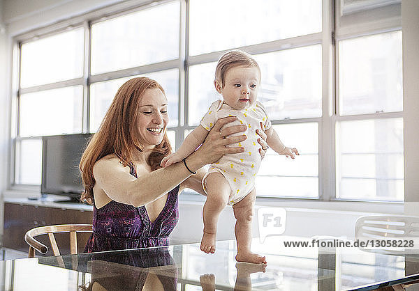 Mother assisting baby girl in walking at home