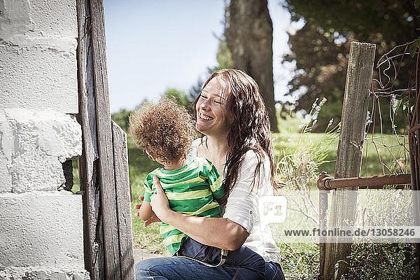 Happy mother embracing son at backyard