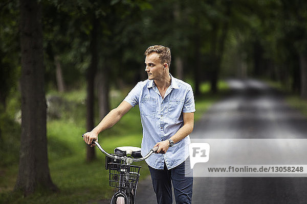 Man looking away while walking with bicycle on road in forest