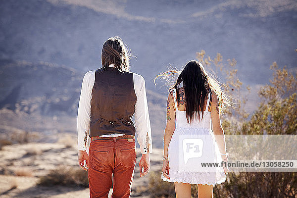 Rear view of couple standing on field