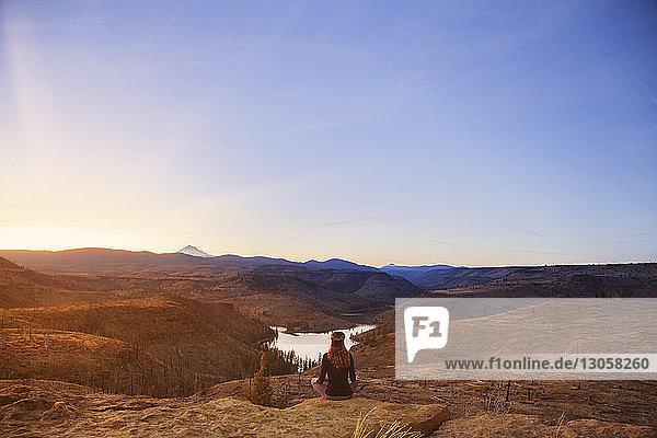 Rückansicht eines Wanderers  der die Berge betrachtet  während er auf einem Fels sitzend vor klarem Himmel