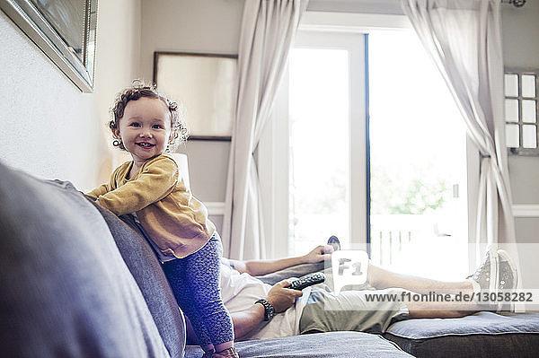 Glückliches Mädchen mit Vater auf dem Sofa zu Hause