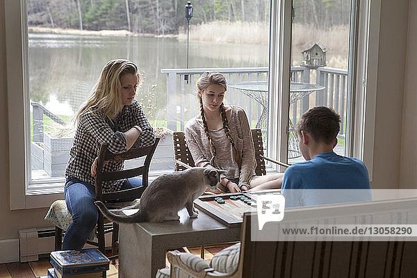Geschwister spielen Backgammon  während sie zu Hause am Fenster sitzen