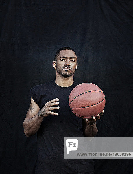 Portrait of man holding basketball while standing against black wall