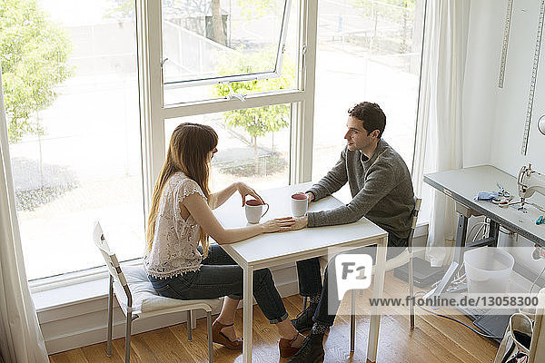 High angle view of colleagues discussing while having coffee at table