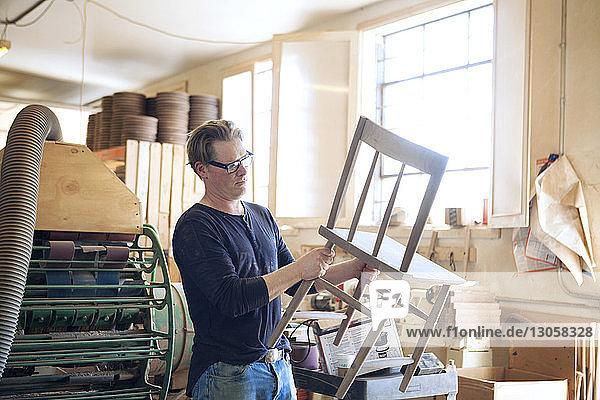 Männlicher Schreiner untersucht Holzstuhl in Werkstatt
