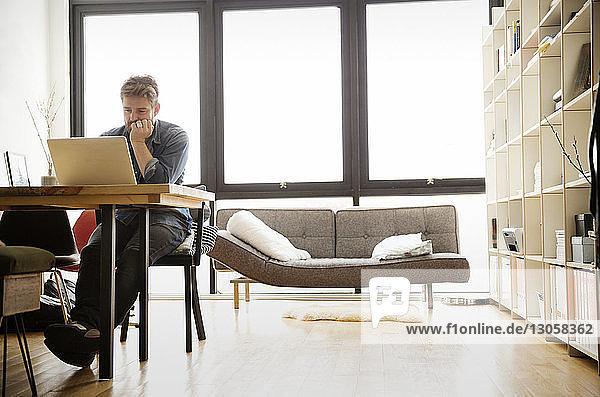 Konzentrierter Mann benutzt Laptop  während er am Tisch sitzt