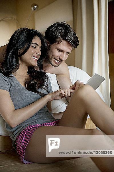Junges Paar benutzt digitales Tablett im Schlafzimmer