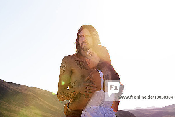 Couple looking away while embracing against clear sky