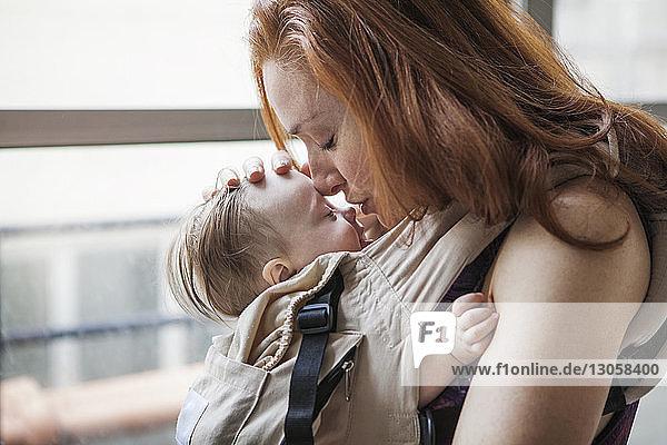 Mutter trägt Tochter in Tragesitz