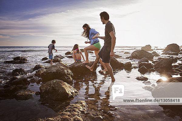Paar  das beim Spaziergang mit spielenden Kindern am Strand Händchen hält