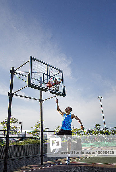 Man dunking ball in hoop at park against sky