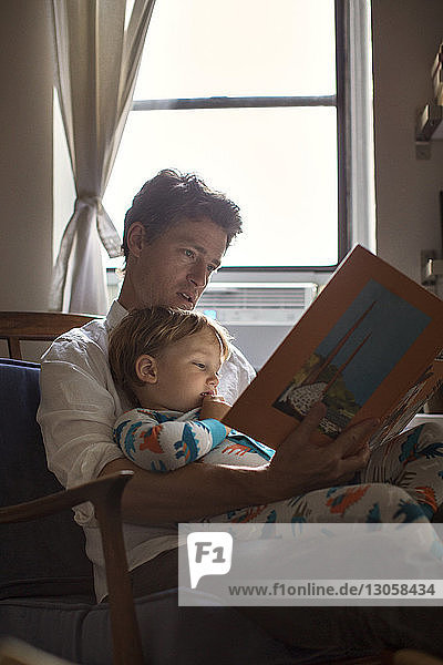 Father reading picture book for son while sitting on chair against window
