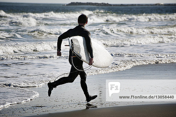 Rear view of surfer carrying surfboard while running on shore at beach