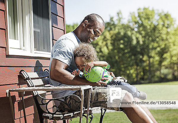 Happy father and son sitting with ball on bench at backyard