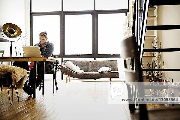 Mann benutzt Laptop  während er am Tisch sitzt